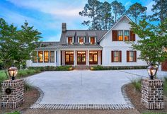 South Carolina low country living  at its finest! Two French Quarter lanterns on post mounts are situated on either side of the driveway leading to this gorgeous home.