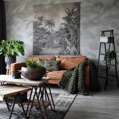 brown leather sofa and plants in the home of yvonne kwakkel