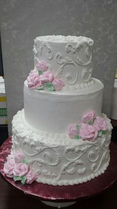 Small three tiered wedding cake in butter cream swirls and pink roses.