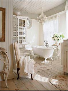 Claw foot bathtub | white drapes | crystal chandelier | big bathroom window