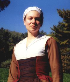Brown Woolen Gown, woolen Flemish Overgown (rust side out), Flemish ruffed partlet, Brown woolen Flemish sleeves, square-necked Flemish chemise, pleated petticoat, stockings, round cap, straw hat