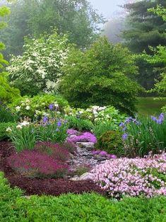 Bel ensemble composé de vivaces à floraison printanière dans les tons de blanc rose bleu. On aime le petit enrochement central laissant imaginer un ébouli.  Www.monjardin-materrasse.com