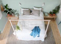Ei seng med naturlige tekstiler i lyse farger mot en lysegrønn vegg i et symmetrisk soverom med lave nattbord og elementer fra naturen