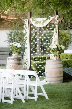 This ceremony altar decor could not get any prettier! Wine barrels, Queen Anne's lace flower arrangements, draped linens and an origami bird curtain! {@clanegessel}