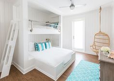 Bunk room with a built-in bed situated under a loft bed with safety rails, both dressed in soft white bedding and turquoise pillows, and fitted with modern ladder situated across from a gray wash dresser alongside a turquoise hex rug next to a Two's Company Hanging Rattan Chair. Laura U, Inc.