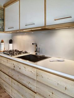 Fascinating way the whitened timber (lye?) has been used horizontally to clad the base kitchen units whilst working with the white wall cupboards above.
