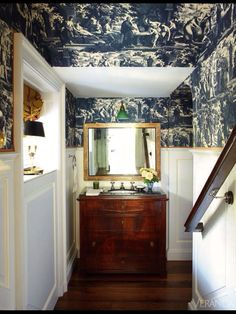 Wow! That navy wallpaper against the white walls and gold mirror. Great!