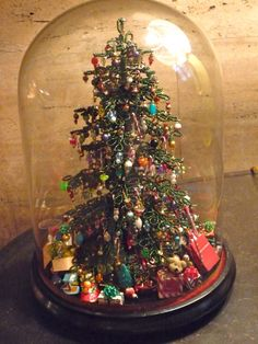 Christmas tree under a cloche. The tree is made of tiny green beads.