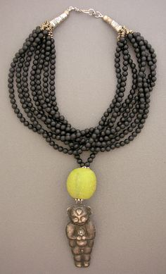 Seven stands of black glass beads from Indonesia hold a dual pendant  made from a very old bead from Java and an antique silver Chinese  child. Sterling silver cones and hook and eye clasp. www.dorjedesigns.com