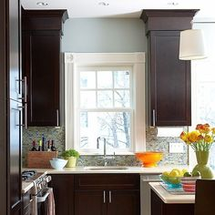 dark kitchen cabinets with blue walls and backsplash