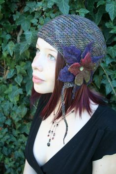 This is a handmade multicolor pixie style ear flap hat crocheted from 100% merino wool yarn. Bold felted flower ensemble makes a statement and