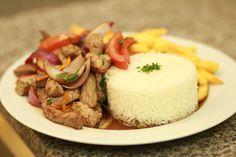 Lomo Saltado, morbida carne di manzo saltao al wok con cipolle e pomodori, salsa di soia, aji amarillo e cipollina.