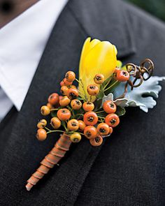 A yellow-and-orange boutonniere made of freesia, pyracantha berries, spray roses, smilax curls, and dusty miller