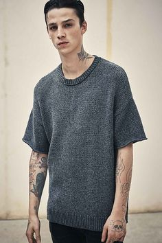 Ash Stymest sports a short-sleeve knit sweater from AllSaints
