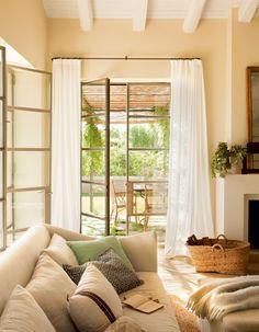 Salón en tonos verdes con amplia ventana con visillos, sofá, chimenea y cesta de fibra_402344