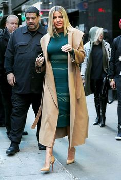 Khloé Kardashian wears a green dress and beige trench coat