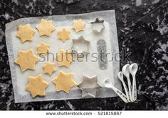 production of Christmas cookies in the shape of stars. raw dough with cookie cutters on a dark background. a New Year style