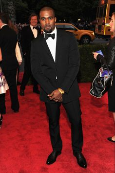 Kanye West, in Givenchy, posed for cameras while flashing a little bit of gold. What, no diamonds, Kanye?
