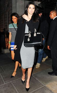 Kendall Jenner wears a grey cotton fitted midi dress, black cardigan, black structured bag, and pointed toe heels.