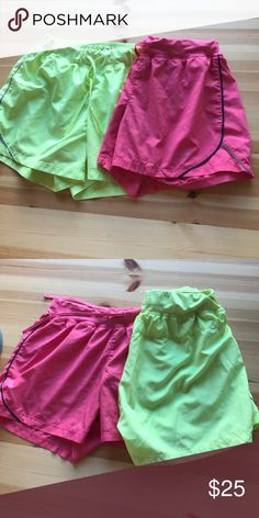 Champion athletic shorts Champion athletic shorts. Bright yellow with gray detail and pink with navy and gray detail. Both size small. They have built in mesh liners. Polyester. Champion Shorts