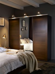 Moody bedroom with Ikea wardrobe and charcoal walls.
