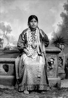 Ho-Chunk woman, Ida Lizzie Decorra Blowsnake (Real Wampum Woman), (WooRooShiekESkaeWinKah)wearing traditional woman's regalia (hinukwaje) made from brightly painted fabric. Solid-color cloth was usually used to make Ho-Chunk women's dresses. Photo: ca. 1900.