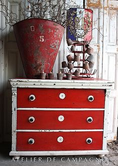 "Red and white chest of drawer with a great patina. A bottle dryer called a ""Herisson"" in French, great decoration item! Find some at www.laboutiquevintage.co.uk And a huge industrial metal container with plant in it, lovely vintage display! #LaBoutiqueVintage"