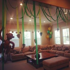 Jungle themed baby shower decorations. Use brown crepe paper as jungle vines and cut huge leaf patterns from green tissue paper and add a few jumbo tissue flowers for color.