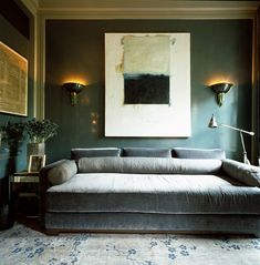 Grey green walls with grey velvet sofa and uplighters either side of art