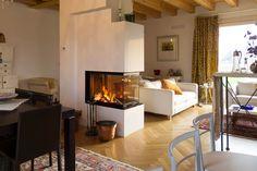 Scopri come un camino trifacciale domina il piano terra, separando la zona pranzo dal living in questa casa singola nell'entroterra veneziano