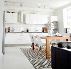 weiße Küche mit Essbereich und hölzernem Esstisch