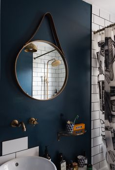 Deep blue wall paint, white metro tiles and brass fixtures make for a striking scheme in the bathroom. The shower curtain is Izola and the bathroom mirror is John Lewis. The glass display shelf is from Rowen &Wren and the toothbrush cup is Pols Potten.