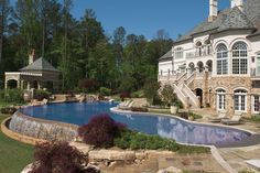 Man-made and natural boulders used in and around the infinity pool accent the waterfall, diving rock, and dramatic 80-foot vanishing edge. Artistic Pools, Inc., Atlanta, Georgia http://www.luxurypools.com/builders-designers/artistic-pools-inc.aspx