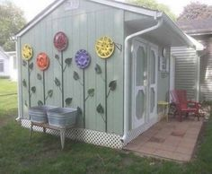 Painted hubcaps make flowers on the side of a shed.