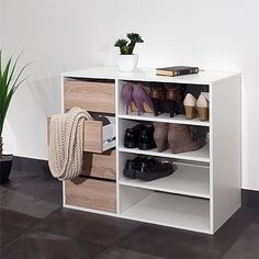 Reynal shoe tidy:4  compartments with 3 adjustable shelves.4 drawers on runners. Reynal shoe tidy:Melamine particle board, thickness 16mm, with a light oak and/or white finish.Choice of 2 finishes : all white or white with light oak coloured drawer fronts.Untreated MDF base. Size of Reynal shoe tidy:Overall size:Length 89.5cm.Depth 39.6cm.Height 73.2cm.Compartment: L51.3 x D39.6 x H15.7cm.Drawer: L29.9 x D36 x H12cm.Made in France.Your Reynal shoe tidy is self-assembly.
