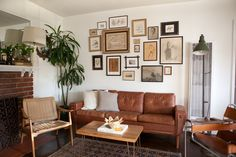 Living room space with leather couch + eclectic gallery wall