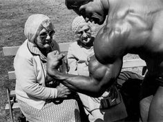 c. 1970s: Arnold Schwarzenegger shows his muscles to some old ladies