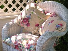 Pretty floral pillows in white wicker chair-(love the way the sunlight casts the shadows on the chair)!