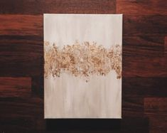 This painting is blended with beautiful shades of white and gold acrylic paint and then dusted with gold leaf. It is painted on a thick heavy duty gallery wrapped canvas and sealed to ensure its look for years to come.
