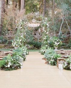 "Adriana and Han exchanged vows in front of an archway of ferns and white blossoms. Floral designer Mindy Rice, who custom-built the decoration, says, ""I combined flowering branches along with soft flowers to make the structure look as though the forest floor had crept in."""
