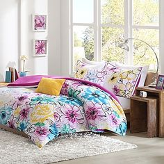 Breathe new life into your bedroom with the beautiful Olivia Reversible Comforter Set. Decked out in an asymmetrical floral design in pops of teal, green, fuchsia and yellow, the lively bedding is an eye-catching addition to any room décor.