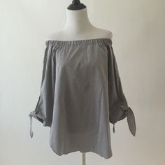 Grey off the shoulder top Just in time for spring / summer!!  Nothing is more of the moment than off the shoulder and this blouse is the perfect combo of feminine and understated sexy.  NWT.  Material is a relatively thinner cotton with no stretch similar to a dress/work shirt.  Color is a light medium gray with bluish undertones. Tops Blouses