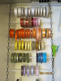 Chain attached to a shelf... dowel rods in the chain to hold Ribbon Spools.