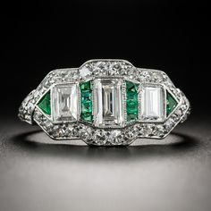 As sleek and sophisticated as they come, this platinum, diamond and emerald sparkler dates from the zenith of the Art Deco period - circa 1925. The streamlined finger-hugger centers on three rectangular-cut diamonds (essentially emerald-cuts without cut corners) interspersed by small electric green calibre-cut emeralds, punctuated on the ends with small triangular emeralds. The center section is bordered all around with a sparkling frame of tiny single-cut diamonds leading to engraved…