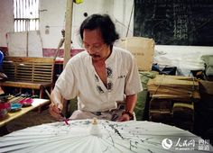 Oil-paper umbrella, living fossil of Chinese folk arts | China Travel & Tourism News Artist painting one of the umbrellas.