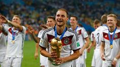 Benedikt Hoewedes of Germany celebrates with the World Cup trophy