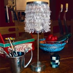 An elegant recycled lamp made from plastic disposable party bowls, an empty bottle of Coke Light, a biscuit tin and tin can.
