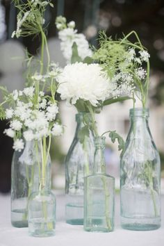 Antique glass bottles and simple white flowers are a lovely combination. #DBBridalStyle