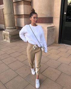 3c7598f93c50 White baggy sweater/sweatshirt, gold drawstring sweatpants, white sneakers,  white side swung Chanel purse, big gold-rimmed vintage glasses