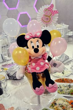 Pink and Gold Minnie Mouse plush toy with small balloons as a table centerpiece
